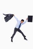 Biznesmena doskakiwanie podczas gdy trzymający jego kurtkę Zdjęcie Royalty Free