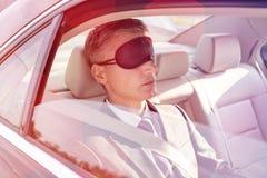 Biznesmena drzemanie podczas gdy b?d?cy ubranym oko mask? w samochodzie fotografia stock