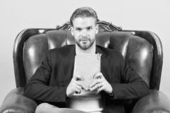 Biznesmena formalny kostium siedzi na rzemiennym krześle, popielaty tło Mężczyzna spokoju twarzy czytelniczej książki studiowanie zdjęcia stock