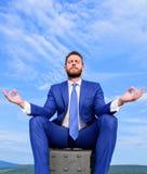 Biznesmena formalny kostium siedzi na teczce i medytować outdoors Mężczyzna próba utrzymywać jego umysł jasny Relaks technika fotografia royalty free