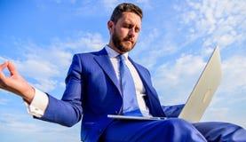 Biznesmena formalny kostium z laptopem medytuje outdoors Mężczyzna próby utrzymanie jego umysł jasny Przedsiębiorcy znaleziska mi fotografia royalty free