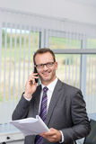 Biznesmena gawędzenie na jego telefonie w biurze Obrazy Stock