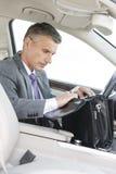 Biznesmena gmeranie w torbie podczas gdy siedzący w samochodzie zdjęcia stock