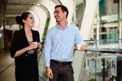 Biznesmena i bizneswomanu stojak i śmiać się z Plastikowym kubkiem na ręce Zdjęcia Stock