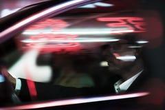 Biznesmena jeżdżenie przy nocy, iluminujących i odbijających światłami na samochodowym okno, Fotografia Stock