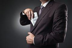 Biznesmena kładzenia pieniądze w jego kieszeni na zmroku Obrazy Stock