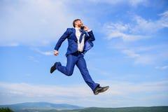 Biznesmena kostiumu formalny skok podczas gdy wywoławczy smartphone nieba tło Biznesmen rozwiązuje biznesowych problemy na telefo obraz stock