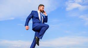 Biznesmena kostiumu formalny skok podczas gdy wywoławczy smartphone nieba tło Przedsiębiorca w ruchu sukcesu wyrażeniu zdjęcia stock