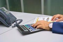 Biznesmena liczenie na kalkulatorze przy biurem Obraz Royalty Free