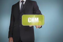 Biznesmena macania zieleni etykietka z słowa crm pisać na nim Obraz Royalty Free