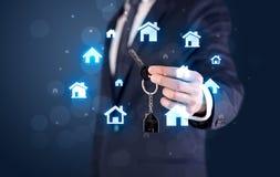 Biznesmena mienia klucze z domami wokoło Zdjęcia Royalty Free