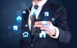 Biznesmena mienia klucze z domami wokoło Obraz Stock