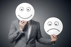Biznesmena mienia uśmiech i smutna maska Konceptualny wizerunek mężczyzna zmienia jego nastrój od złego dobry zdjęcie stock