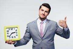 Biznesmena mienie zegarowy i seansu kciuk up Obraz Stock