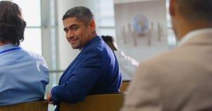 Biznesmena obsiadanie i ono uśmiecha się w biznesowym konwersatorium 4k zbiory