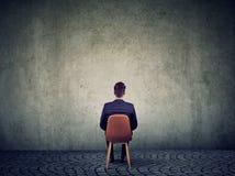 Biznesmena obsiadanie na krześle przed betonową ścianą rozwiązuje problem fotografia stock