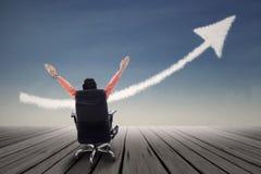 Biznesmena obsiadanie na krześle z nastroszonymi rękami i up strzała podpisujemy Obraz Stock