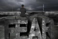Biznesmena obsiadanie na strachu słowa burzy okładzinowym ciemnym oceanie Obrazy Royalty Free