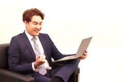 Biznesmena obsiadanie poza zaciska jego pięść po sprawdzać pomyślnego biznesowego rezultat na internecie na czarnej kanapie, szcz zdjęcie royalty free
