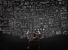 Biznesmena obsiadanie przed blackboard z mapami Zdjęcie Stock