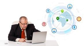 Biznesmena obsiadanie przy biurkiem i przyglądającym laptopem z kulą ziemską i w ten sposób Obrazy Royalty Free