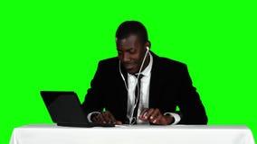 Biznesmena obsiadanie przy biurkiem i słuchanie muzyka na hełmofonach zielony ekran zbiory wideo