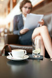 Biznesmena obsiadanie w hotelu kuluarowym używa telefonie komórkowym laptopie i Fotografia Royalty Free
