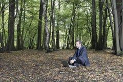 Biznesmena obsiadanie Z laptopem Na ziemi W lesie Zdjęcia Stock