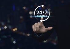 Biznesmena odciskania guzik 24 godziny usługowej ikony nad plamy ligh Obraz Royalty Free