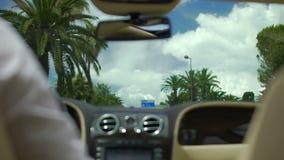 Biznesmena oddawania dom w luksusowym samochodzie po pracy, napędowa ulica z palmami zbiory