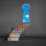 Biznesmena pięcie na stert książkach wpisywać kształta drzwi Obrazy Royalty Free