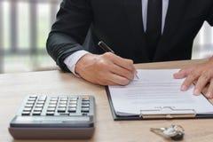 Biznesmena podpisywania kontrakt z kluczem i kalkulator na drewnianym d Zdjęcie Royalty Free