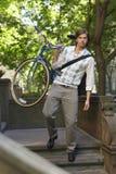 Biznesmena przewożenia bicykl Podczas gdy Pochodzący kroka Obraz Stock