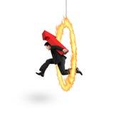 Biznesmena przewożenia czerwonej strzała up szyldowy doskakiwanie przez pożarniczego obręcza fotografia stock
