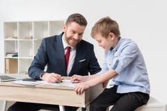 Biznesmena rysunek na biznesowych papierach z synem Obraz Royalty Free