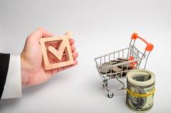 Biznesmena ` s ręka trzyma drewnianego checkbox blisko monet i tramwaju Pojęcie zatwierdzenie i przyciąganie inwestycje zdjęcia stock