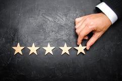 Biznesmena ` s ręka w kostiumu trzyma kwinty gwiazdę Dostaje kwinty gwiazdę Pojęcie ocena hotele i restauracje Obrazy Stock