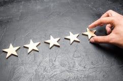 Biznesmena ` s ręka w kostiumu trzyma kwinty gwiazdę Dostaje kwinty gwiazdę Pojęcie ocena hotele i restauracje Obraz Royalty Free
