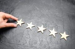 Biznesmena ` s ręka w kostiumu trzyma kwinty gwiazdę Dostaje kwinty gwiazdę Pojęcie ocena hotele i restauracje Fotografia Royalty Free