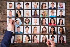 Biznesmena ` s ręka Wybiera fotografię kandydat Na biurku zdjęcia stock
