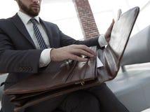 Biznesmena ` s ręka z suitecase w nowożytnym biurze Zdjęcie Stock