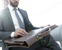 Biznesmena ` s ręka z suitecase w nowożytnym biurze Obraz Royalty Free