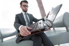 Biznesmena ` s ręka z suitecase w nowożytnym biurze Fotografia Royalty Free