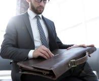 Biznesmena ` s ręka z suitecase w nowożytnym biurze Fotografia Stock