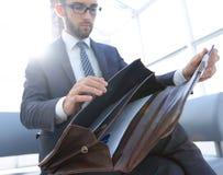 Biznesmena ` s ręka z suitecase w nowożytnym biurze Obraz Stock