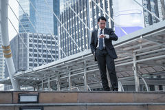 Biznesmena spojrzenie jego zegarek i stojak na ziemi z nowożytnym buil Zdjęcia Royalty Free