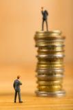 Biznesmena stojak dla zegarka i wyzwanie biznes na monetach obrazy stock