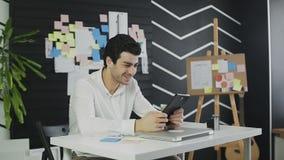 Biznesmena szczęśliwie spojrzenia przy pastylką śmia się od co widzii na ekranie zdjęcie wideo