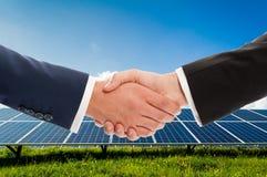 Biznesmena uścisk dłoni na solarpower photovoltaic panelu backgroun Obrazy Stock
