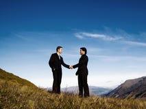 Biznesmena uścisku dłoni pasma górskiego osiągnięcia pojęcie obrazy royalty free